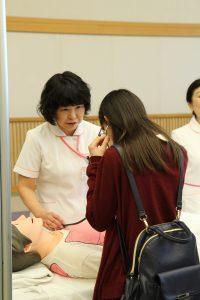 聴診器で人型模型の音を聞く体験